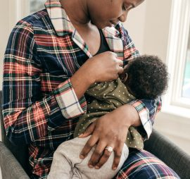 mother in plaid shirt nursing a baby